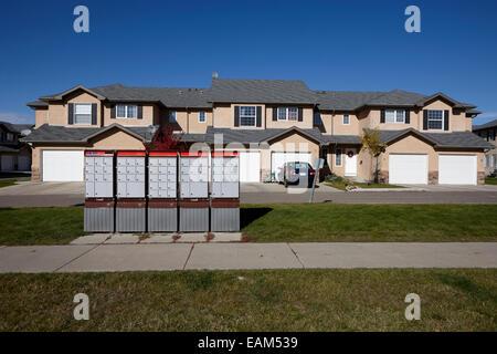 row of canada post mailboxes on sidewalk in suburban neighbourhood saskatoon Saskatchewan Canada - Stock Photo