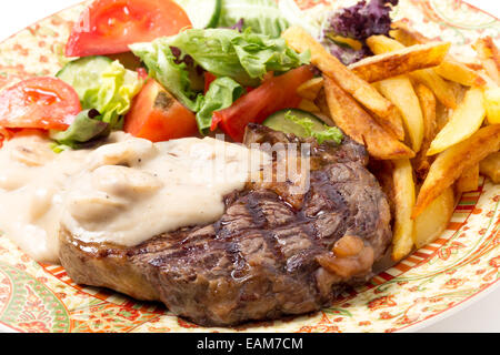 Grilled rib-eye beef steak served with mushroom sauce, salad and potato chips. - Stock Photo