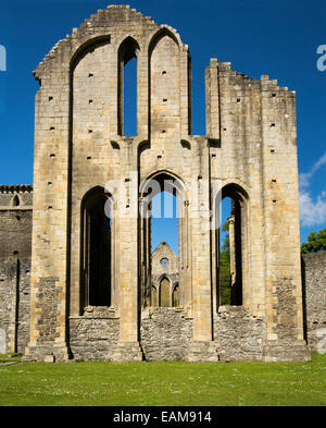 High and ornate facade of 13th century Valle Crusis abbey ruins rising from emerald grass to blue sky  near Llantysilio - Stock Photo