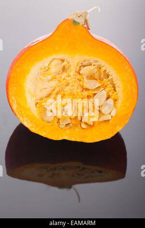 Half Red kuri squash, a small japanese  pumpkin with reflection over a glass background - Stock Photo