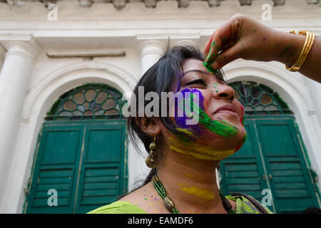 An Indian Woman applying colors on a face of another woman , Kolkata, West Bengal, India - Stock Photo