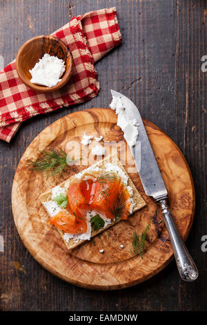 Sandwich on Crisp bread with Smoked salmon and soft Cream cheese on Olive wood plate - Stock Photo