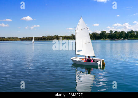 Small white boat sailing on the lake on a beautiful sunny day - Stock Photo