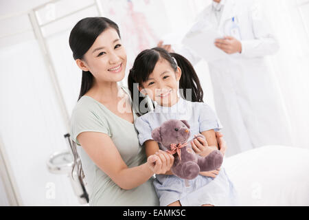 Mother hug the girl and the doctor in the ward - Stock Photo