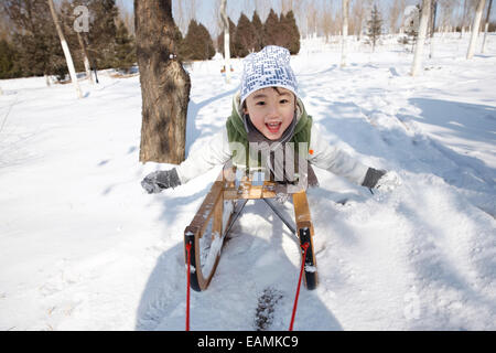 The little boy on the sled - Stock Photo