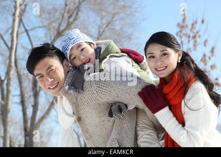 Mother and father carrying his son in the outdoors - Stock Photo