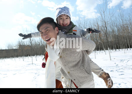 Father with his son and mother running in the snow - Stock Photo