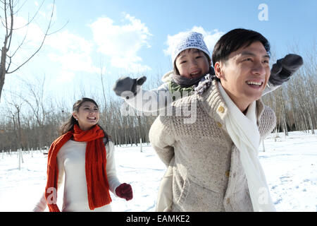 A family of three running in the snow - Stock Photo