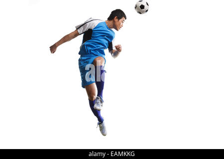 A football player jumps in mid air header - Stock Photo