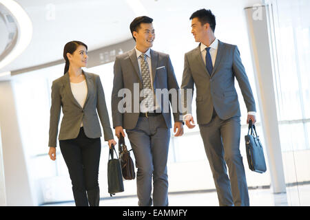Oriental business people talk while walking - Stock Photo