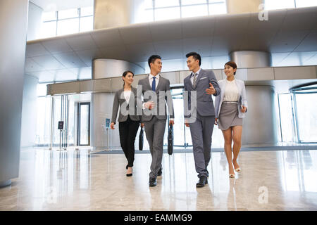 Four business people talk while walking - Stock Photo