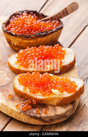 Sandwiches with Salmon red caviar on wooden background - Stock Photo