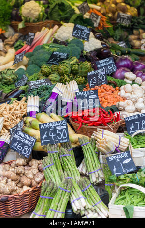 A selection of vegetables priced up and displayed on a market stall including asparagus, chillies, and jerusalem - Stock Photo
