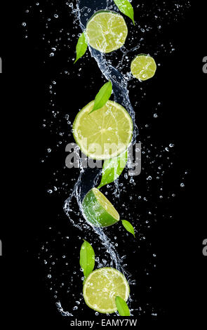 Limes in water splash, isolated on black background - Stock Photo