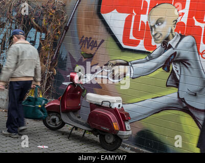 Frankfurt Main, Germany. 18th Nov, 2014. A man with giant scissors on a graffiti 'cuts' the handlebars of a parked scooter in Frankfurt Main, Germany, 18 November 2014. Photo: FRANK RUMPENHORST/dpa/Alamy Live News Stock Photo
