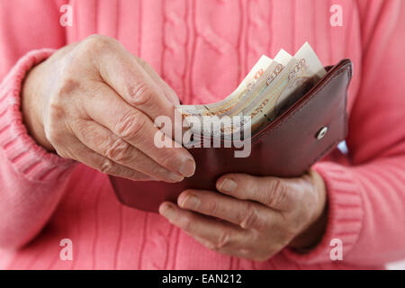 Elderly senior woman old age pensioner taking ten pound notes GBP out of a money wallet to buy and pay for something - Stock Photo
