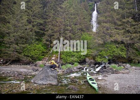 Sea Kayaker Sits On A Rock And Enjoys A Unnamed Waterfall, Kachemak Bay State Park, Kenai Peninsula Alaska During - Stock Photo
