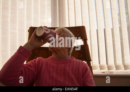 Elderly woman drinking a tea from a take away container - Stock Photo