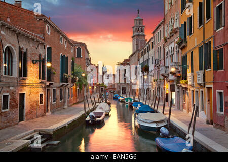 One of many narrow canals in Venice during beautiful sunset. - Stock Photo