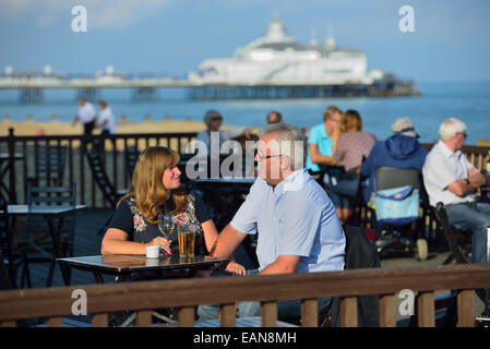 Adult couple enjoying an early evening drink together at a beach cafe on the seafront at Eastbourne. East Sussex. - Stock Photo