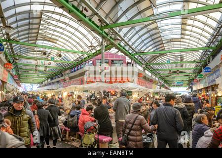 Shoppers in Seoul, South Korea pass through Gwangjang Traditional Market. - Stock Photo