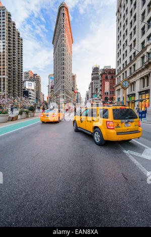 Taxis stop under the Flatiron Building in New York City. - Stock Photo