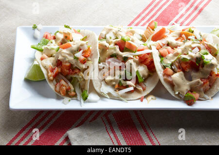 Lobster Tacos on a white plate with a red stripe napkin - Stock Photo