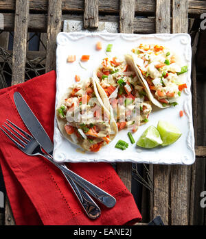 Lobster Tacos on a white plate with a red napkin - Stock Photo