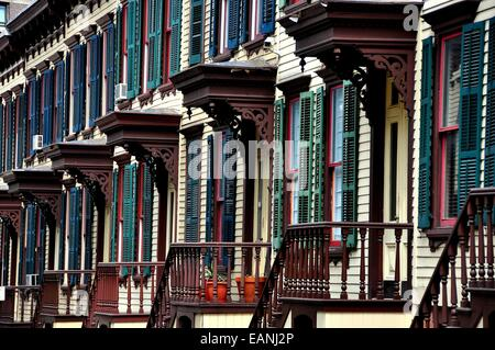 NYC:  1882 two story wooden row houses with shutters, stairway balustrades, and doorway overhangs on Sylvan Terrace - Stock Photo