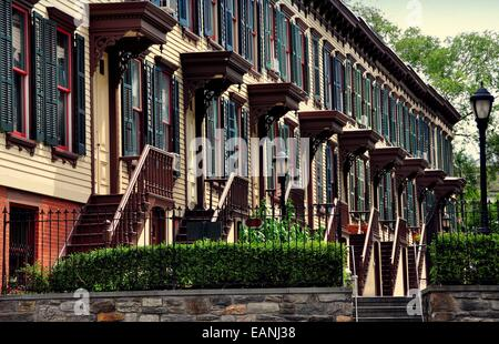 NYC:  1882 two story wooden row houses with stairway stoops and basement entry doors on Sylvan Terrace - Stock Photo