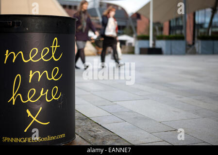 'Meet Me Here' sign on side of garbage bin with two blurred female adults walking in background, Manchester, UK - Stock Photo