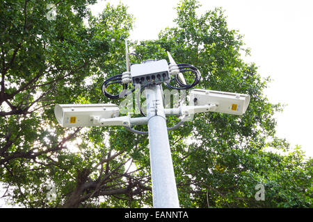 two security surveillance cameras near green forest. - Stock Photo