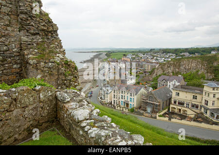 View, from hilltop castle, of historic Welsh town of Criccieth with row of houses by road bordering sandy beach - Stock Photo