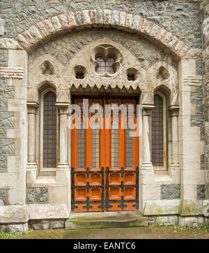 Ornate double timber doora with glass panels & spectacular decorative stonework at entrance to historic building - Stock Photo