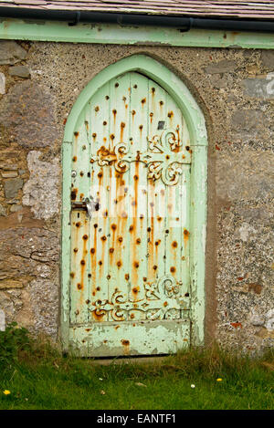 Old door with weathered green paint & huge decorative hinges at historic Saint Tudno's church on Great Orme, Llandudno, - Stock Photo