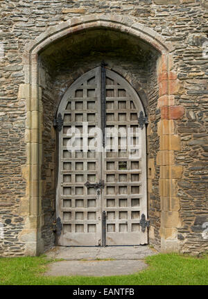 High old double doors with lattice pattern in arched stone alcove in walls of ancient ruins of  Valle Crusis abbey, - Stock Photo