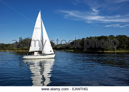Small and medium size sailboats ply the waters of the Chiemsee, or Bavarian Sea. - Stock Photo