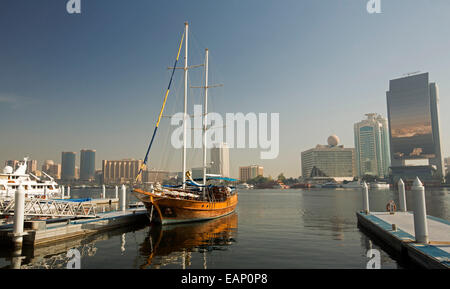 Wooden yacht moored & reflected in calm blue water of Dubai Creek with glass walled skyscraper & other modern buildings - Stock Photo