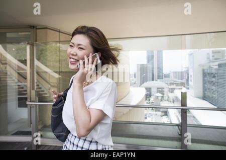 A woman on a walkway in Namba Park office and shopping complex. - Stock Photo