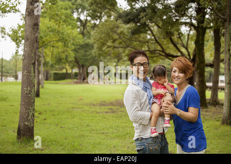 Family in a park. Two parents and a toddler. - Stock Photo