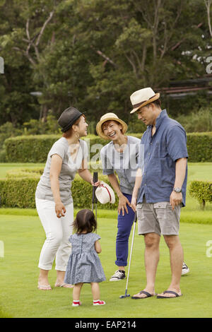Family on a golf course.A child and three adults. - Stock Photo