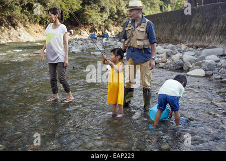 Family fishing in a stream. - Stock Photo