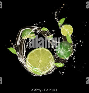 Fresh limes in water splash, isolated on black background - Stock Photo