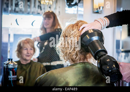 Reflection of hairdresser scrunching a blond lady's hair - Stock Photo