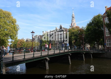 Old bridge at Kloveniersburgwal canal between Raamgracht and Rusland in  Amsterdam, with tower of 17th century Zuiderkerk - Stock Photo