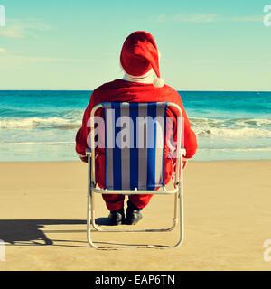 santa claus sitting in a beach chair on the beach - Stock Photo