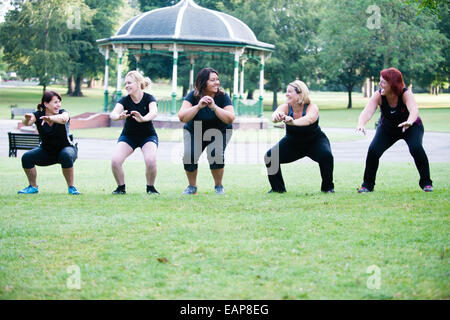 Five white overweight women in gym clothese having fun at a boot camp exercising in a park early in the morning - Stock Photo
