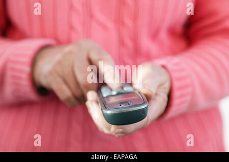 A right-handed senior old woman using a touch phone handset keypad to dial a telephone number to make a phone call - Stock Photo