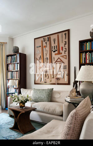 A box frame displaying a variety of tools - paintbrushes, wooden set squares and picture chains - on a living room - Stock Photo
