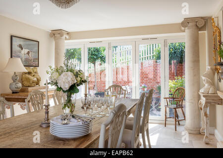 Teak top dining table in neoclassical feeling dining room with french windows and columns - Stock Photo